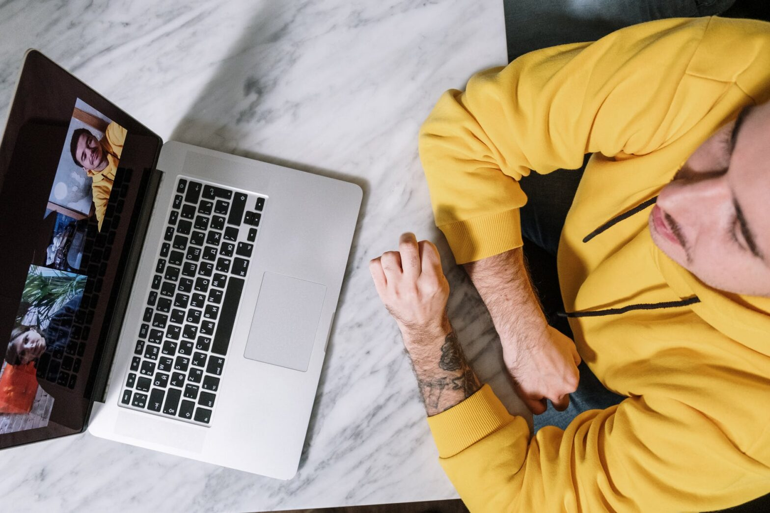 person in yellow long sleeve shirt using macbook pro